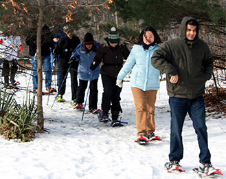 People walking on snowshoes at Harris Nature Center